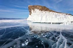 Baikal Lake at February sunny day. Blue smooth ice with bubbles and cracks near the beautiful iced Kobyliya Golova Cliff - a natural landmark of Olkhon Island. Beautiful landscape, winter background