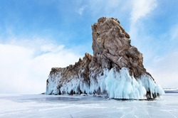 Baikal Lake. Beautiful Ogoy Island with blue ice crust and icicles on coastal rocks on a winter sunny day. Cape Dragon - a natural landmark and a place of tourist excursions