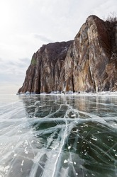 Baikal Lake on a winter day. View from the ice to the beautiful rocks of the famous Cape Sagan-Zaba with ancient rock paintings. Winter travel on ice. Natural background
