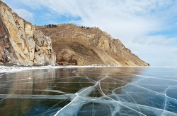 Baikal Lake on sunny frosty day in February. Beautiful smooth transparent ice near the rocks of the famous Sagan-Zaba Сape with ancient rock paintings. Ice travel. Natural background. Winter landscape