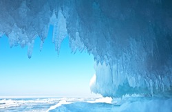 Baikal Lake. Thick blue ice and icicles on the coastal rocks of Olkhon Island in winter. Natural cold background
