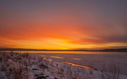 Baikal region. Late autumn. Orange sunset reflected in the water. The water in the lake began to freeze.