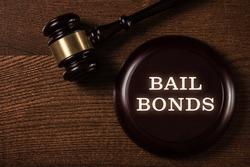 Bail bonds services concept. Judge gavel on wooden background.