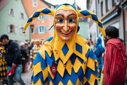 Bajass from Waldkirch - beautiful fool figure in a yellow-blue robe with a curious expression on the carnival parade in Staufen, southern Germany