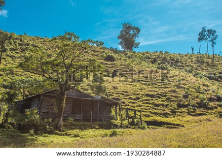 Bajos del Toro, Alajuela, Costa Rica. Log cabin in the middle of the field and green pasture on a sunny day with blue sky Foto stock ©