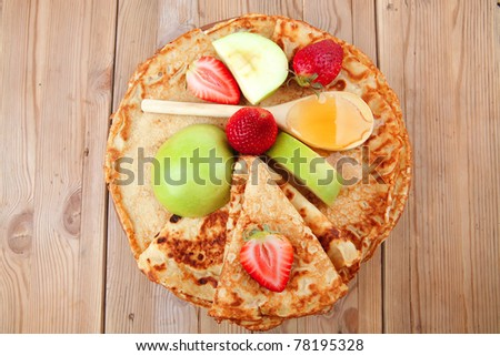 baked and fruits : pancake with honey strawberries and apple on wooden table