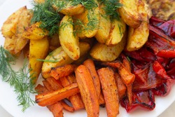 Baked and grilled vegetables plate closeup with carrots, potatoes and bell pepper. Fresh dill on top. Vegetarean snack closeup.