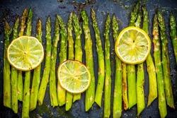 baked asparagus with lemon on a dark background