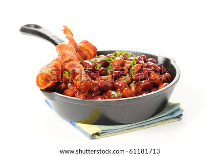 Baked beans and bacon served in a cast iron skillet.