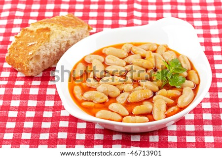 Baked beans and parsley in tomato sauce over a wood background. Shallow depth of field