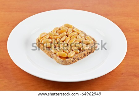 Baked beans in tomato sauce over a wood background. Shallow depth of field