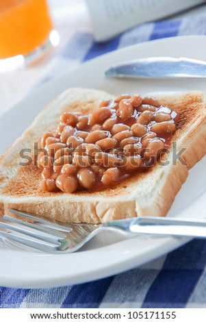 Baked beans on a slice of toasted bread on a white plate with breakfast table setting