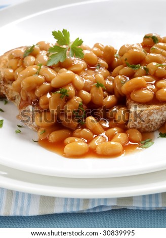 Baked beans on sourdough toast, garnished with parsley.