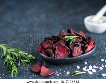 Baked beet slices with coarse sea salt scented rosemary. Vegan diet food idea and recipe. Healthy homemade beetroot chips in plate and ingredients on dark blue background. Copy space
