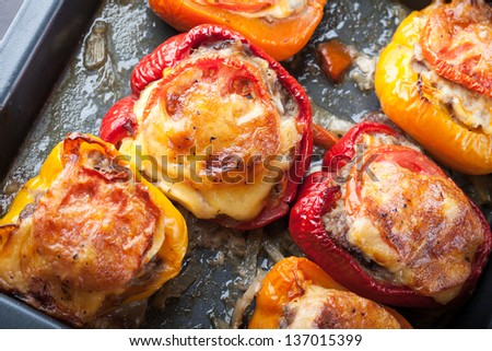 Baked bell peppers stuffed with chopped meat on black baking pan