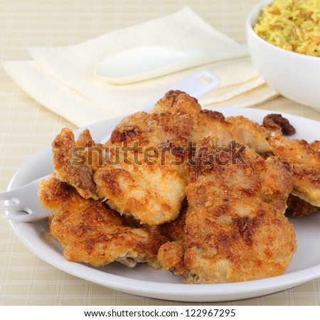 Baked breaded chicken thighs on a serving plate