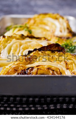 Baked cabbage pieces on a metal plate on a dark background. Selective focus. #434144176