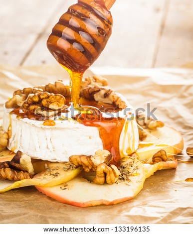 Baked camembert with apples dipped with honey and walnuts