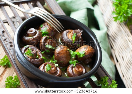 Stock Photo Baked champignons mushrooms with butter, parsley and roasted garlic in black bowl. Selective  focus. Healthy food concept.