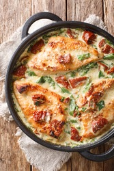 Baked chicken fillet in a creamy sauce with sun-dried tomatoes and spinach close-up in a pan on the table. Vertical top view from above