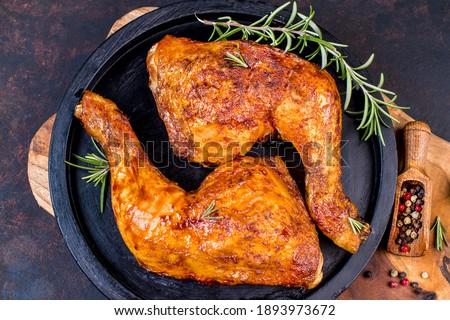 Baked chicken legs in a ceramic black baking dish on a wooden kitchen board. Grilled chicken, grilled chicken legs.