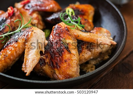 Baked chicken wings in pan on wooden table. #503120947
