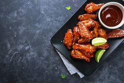 Baked chicken wings with sesame and sauce. Food background with copy space. Top view