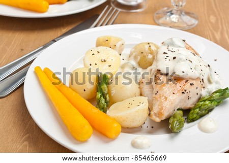 Baked chicken with creamy asparagus sauce served with potatoes and carrots