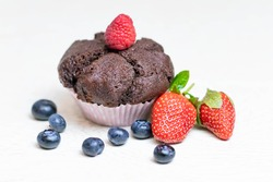 Baked chocolate muffin with juicy berries, strawberries, blueberries, raspberries