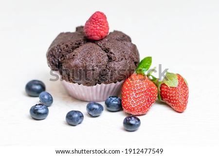 Baked chocolate muffin with juicy berries, strawberries, blueberries, raspberries Photo stock ©