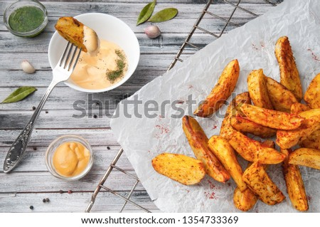 Baked country style potatoes with spicy herbs on white craft paper. With cheese sauce, mustard and pesto. A slice of potatoes on a fork in the sauce. Wooden gray background. View from above. Stock photo ©