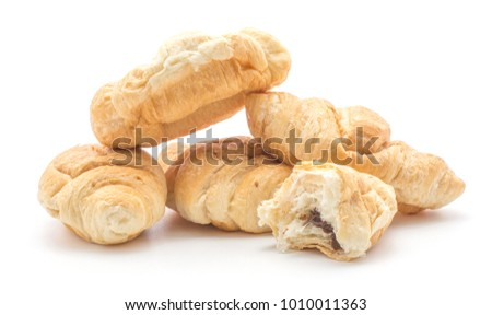 Baked croissants or cornetto stack isolated on white background four whole and one broken half with chocolate cream inside