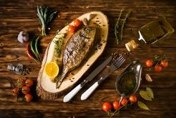 baked dorado \ dorada fish on a dark wooden background, top view
