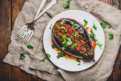 Baked eggplant stuffed with ground beef, tomatoes and spices on white plate. Traditional dish Karniyarik of turkish cuisine. View from above