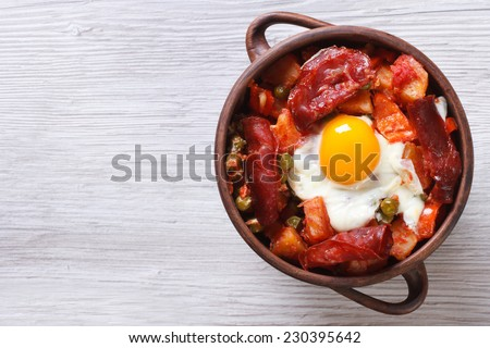 baked eggs with chorizo, potatoes and tomatoes in a pot on the table. close up top view, horizontal