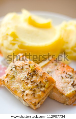 Baked fillet and mashed potatoes with cumin selective focus on the fillet