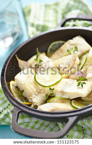 Baked fish fillet with lemon, lime, garlic and thyme
