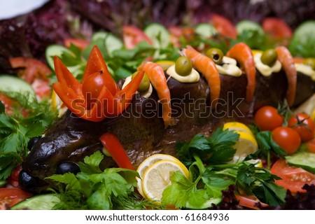 baked fish full body on plate in restaurant