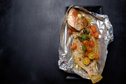 Baked fish with tomatoes, herbs and spices, home cook dish on aluminum foil.