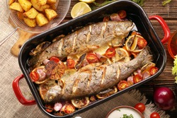 Baked fish with vegetables and potatoes in pan on wooden background