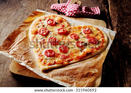 Baked heart-shaped homemade pizza topped with mozzarella and tomato slices, on parchment paper on a cutting board near a checkered red and white kitchen towel, on a rustic table, high-angle close-up
