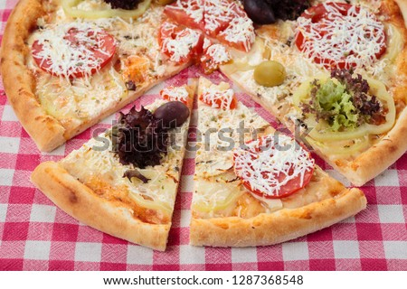 Baked hot vegetarian pizza. Vegetarian pizza on a red classic checkered tablecloth #1287368548