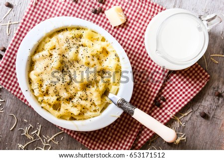 Baked macaroni and cheese dish with parmesan and cream sauce in a pan on a wooden table, top view