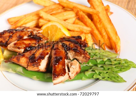 Baked, marinaded chicken breasts with orange and soy sauce, served with french fries on a bed of asparagus