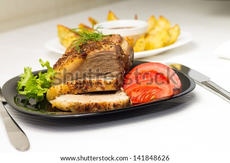 Baked Meat with Grilled Potato and Tomato on Served White table
