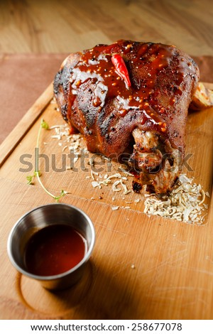 Baked meat with red chili pepper on wooden board closeup