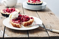 Baked mini tarts with raspberries on a rustic wooden table.