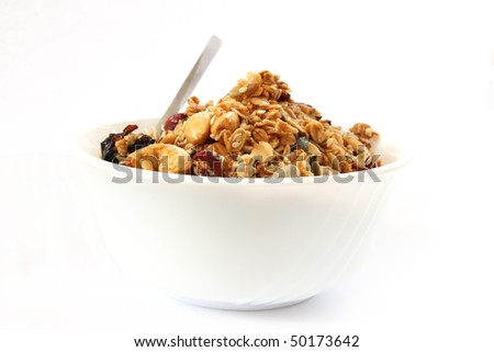 Baked muesli in white bowl with fruit and nuts on white background with a spoon