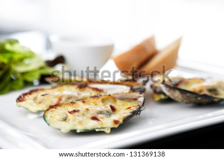 Baked mussels au gratin with salad and sauce.