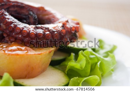 Baked octopus with potatoes on lettuce leaf